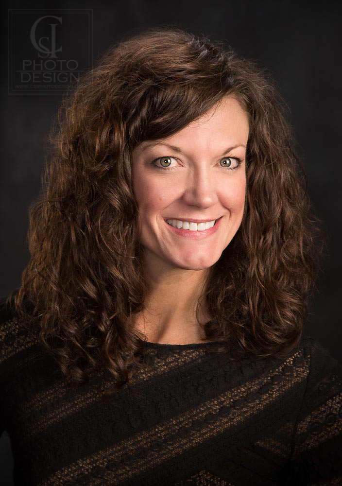 Business woman with curly hair on a dark background