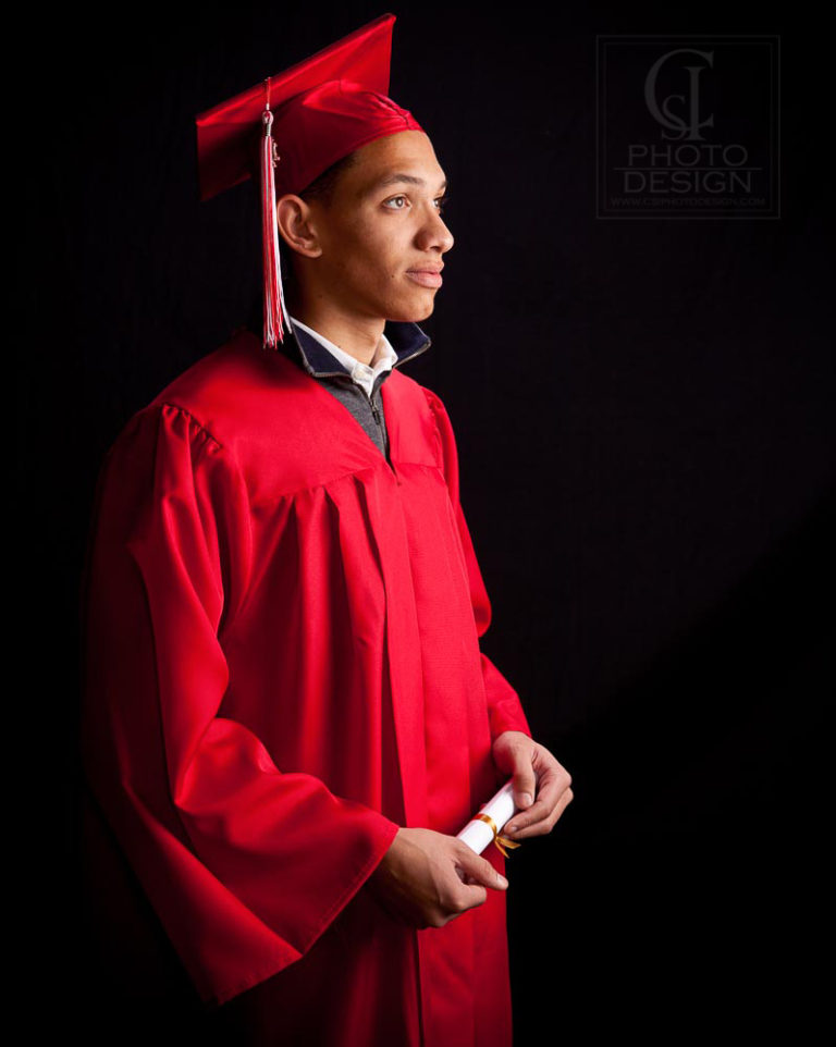 Senior boy in red graduation robes and cap on black background
