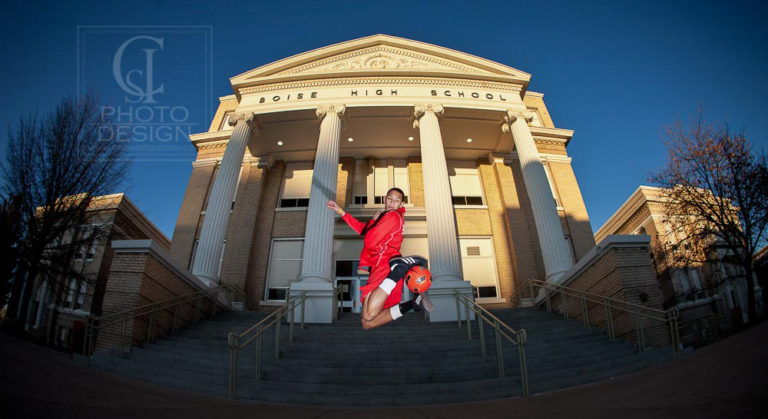 Senior boy leaping with soccor ball in front of Boise High School