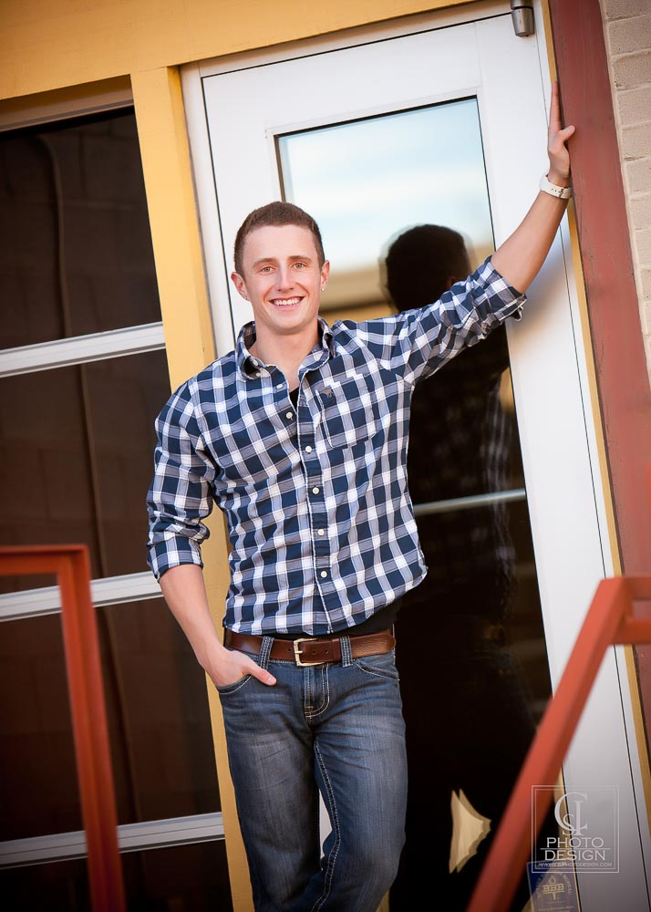 Senior boy in plaid with red railing and gold walls