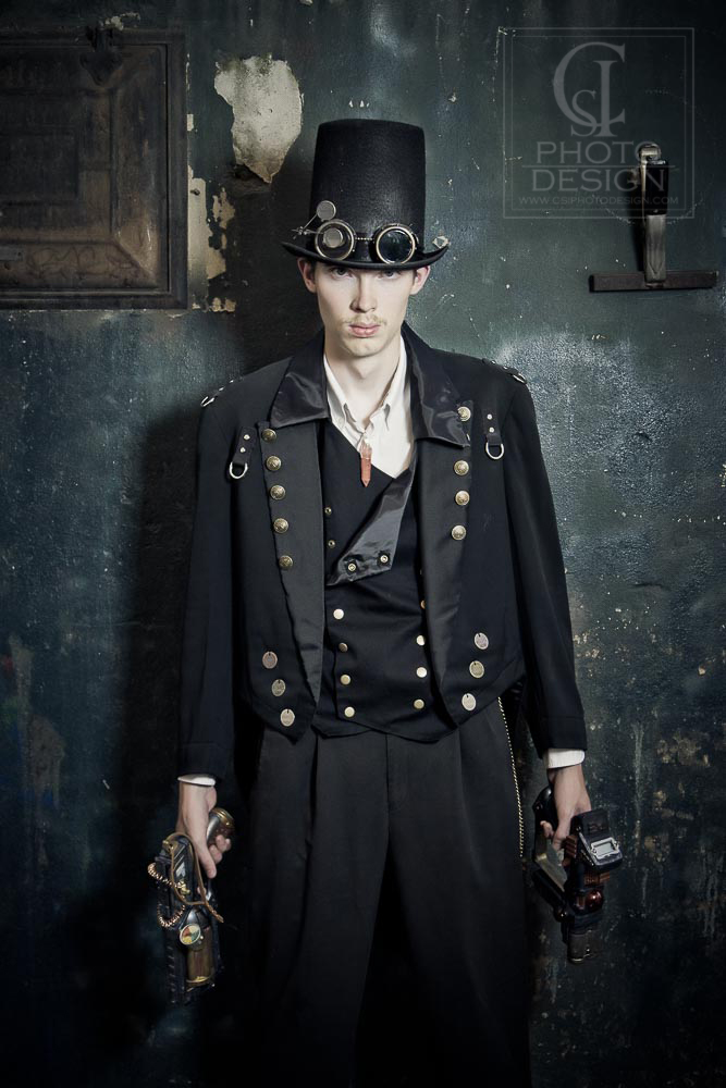 Senior boy in steampunk costume in front of a green wall