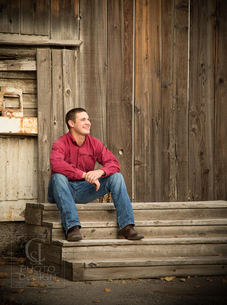 Senior boy on wooden steps and weathered wood background