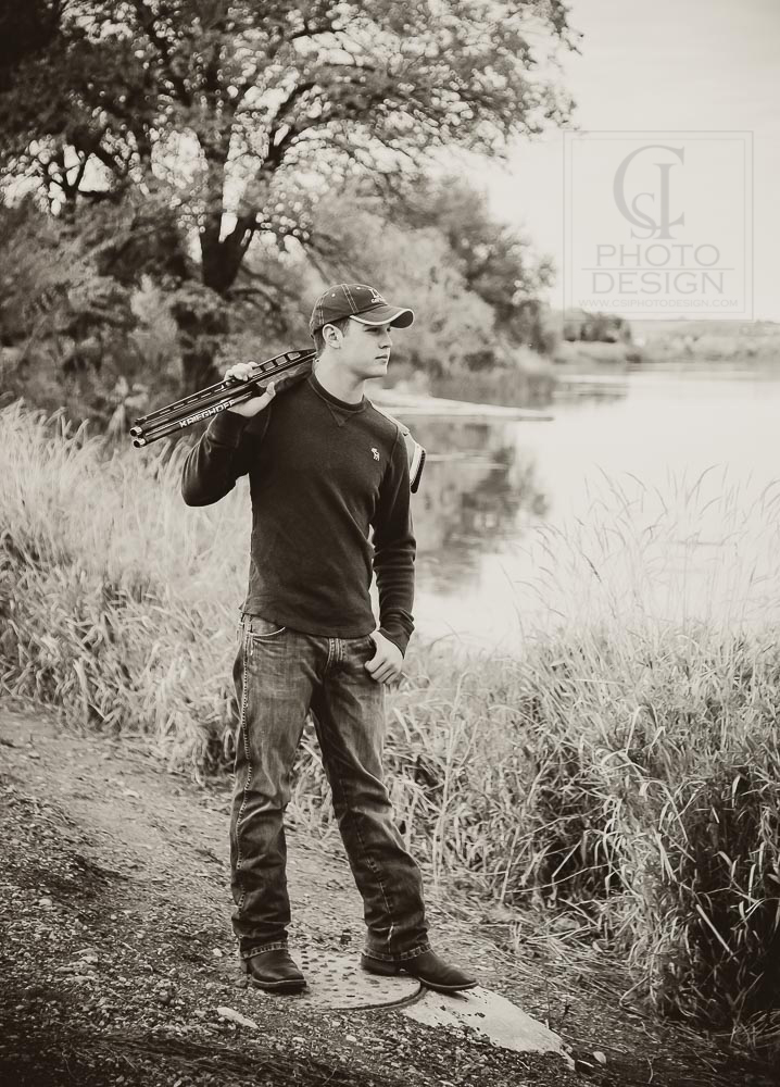 Senior boy with shotgun standing on the bank of the Snake River