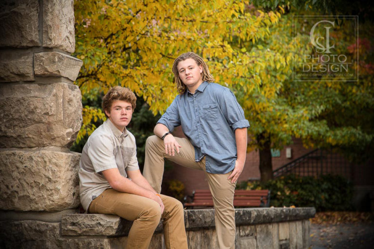Senior boys with fall leaves and sandstone bench