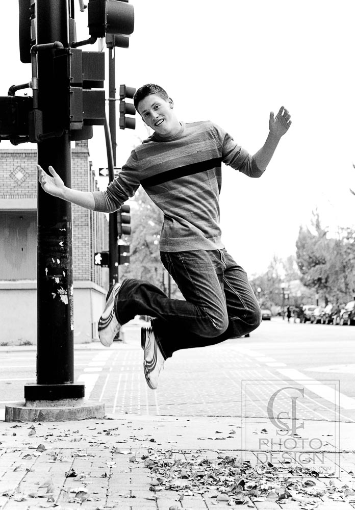 Senior boy leaping on a street corner