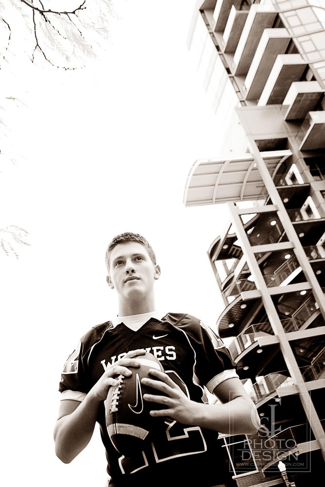 Senior boy in football jersey and football in front of apartment high-rise