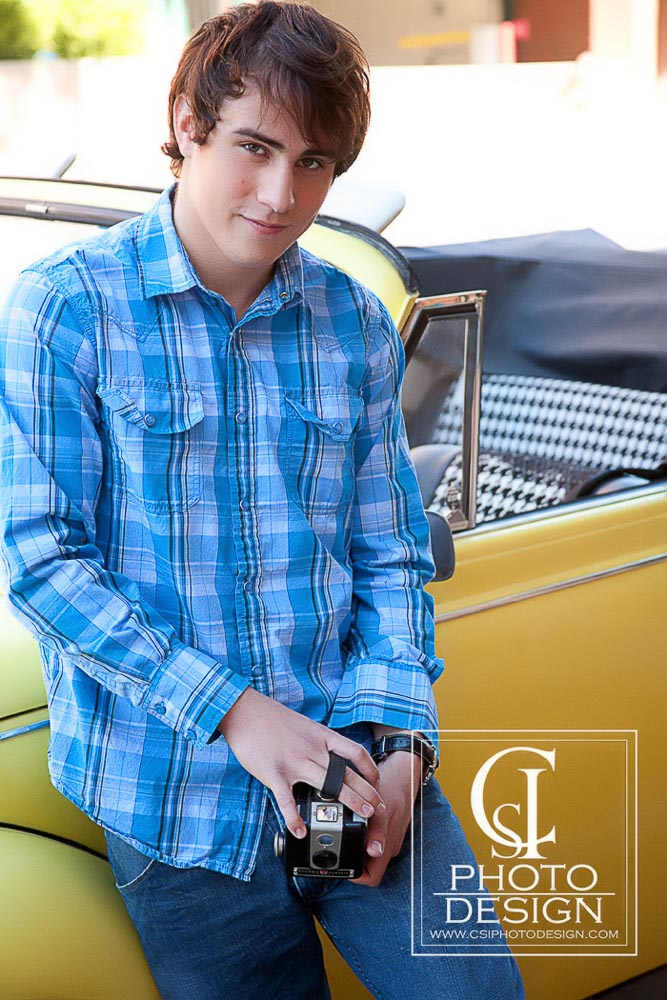 Senior boy in a blue shirt with yellow VW convertible