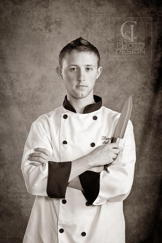 Senior boy in chef uniform with chef knife