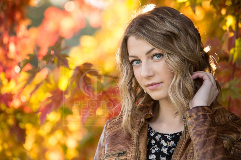 Senior girl in brown leather jacket and fall leaves