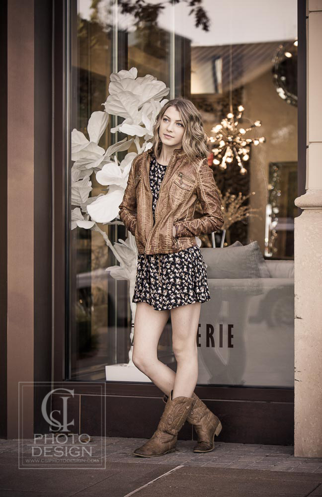Senior girl in floral dress boots and leather jacket in front of store window