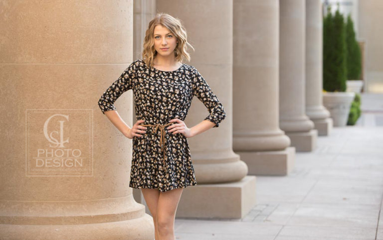 Senior girl in floral dres standing in front of large columns
