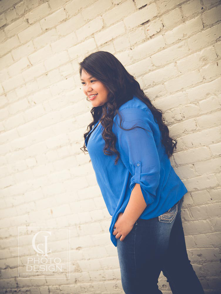 Senior girl in blue top and jeans in front of white brick wall