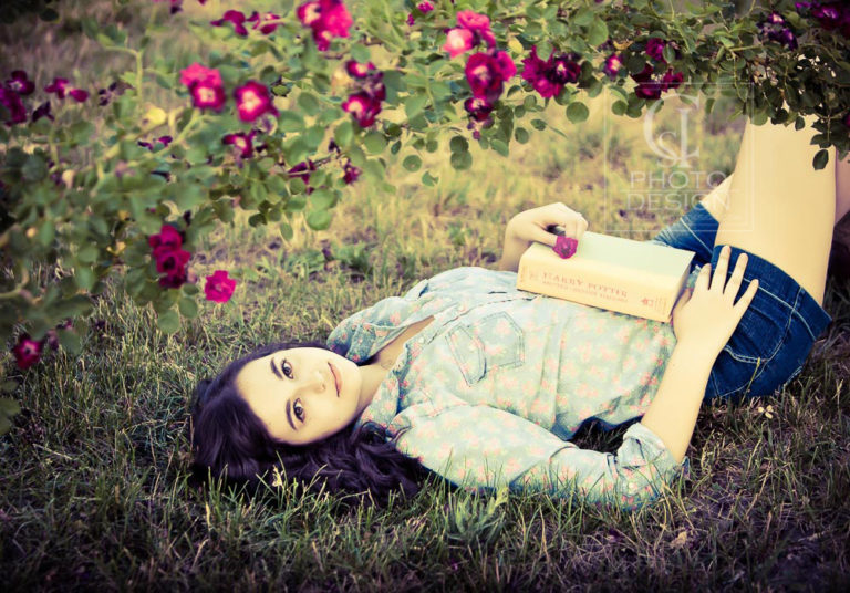 Senior girl with Harry Potter book on the grass framed with flowers