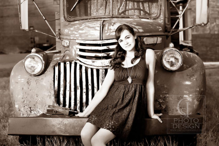 Senior girl in a dress sitting on the bumper of an old truck