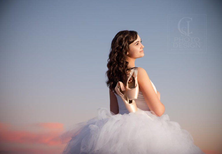 Senior girl with ballet shoes and tutu against an evening sky