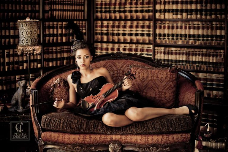 Senior girl with a black dress on an ornate cough with violin in a library