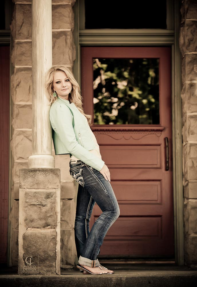 Senior girl in green jacket and jeans on the patio of a sandstone house with a red door