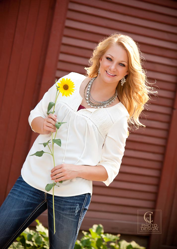 Senior girl in a white top with a sunflower against a red building