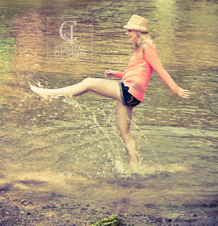 Senior girl splashing in the river in shorts and straw hat