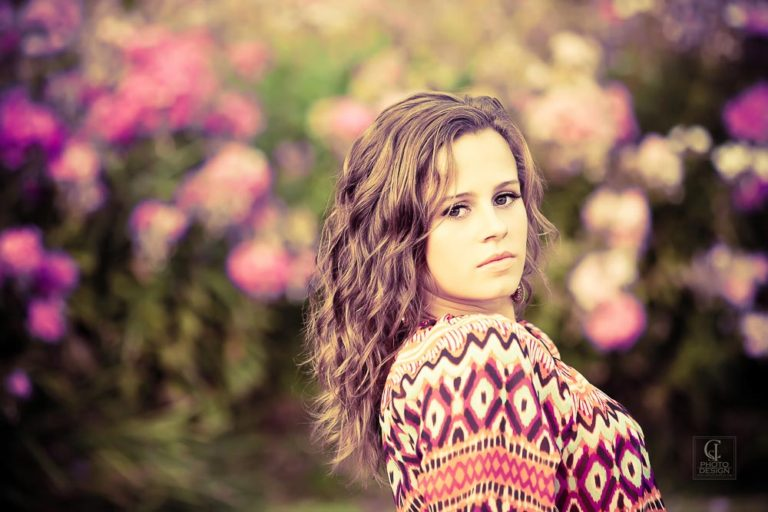 Senior girl in patterned top with a background of flowers