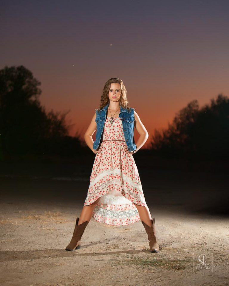 Senior girl in floral dress and denim vest at twilight