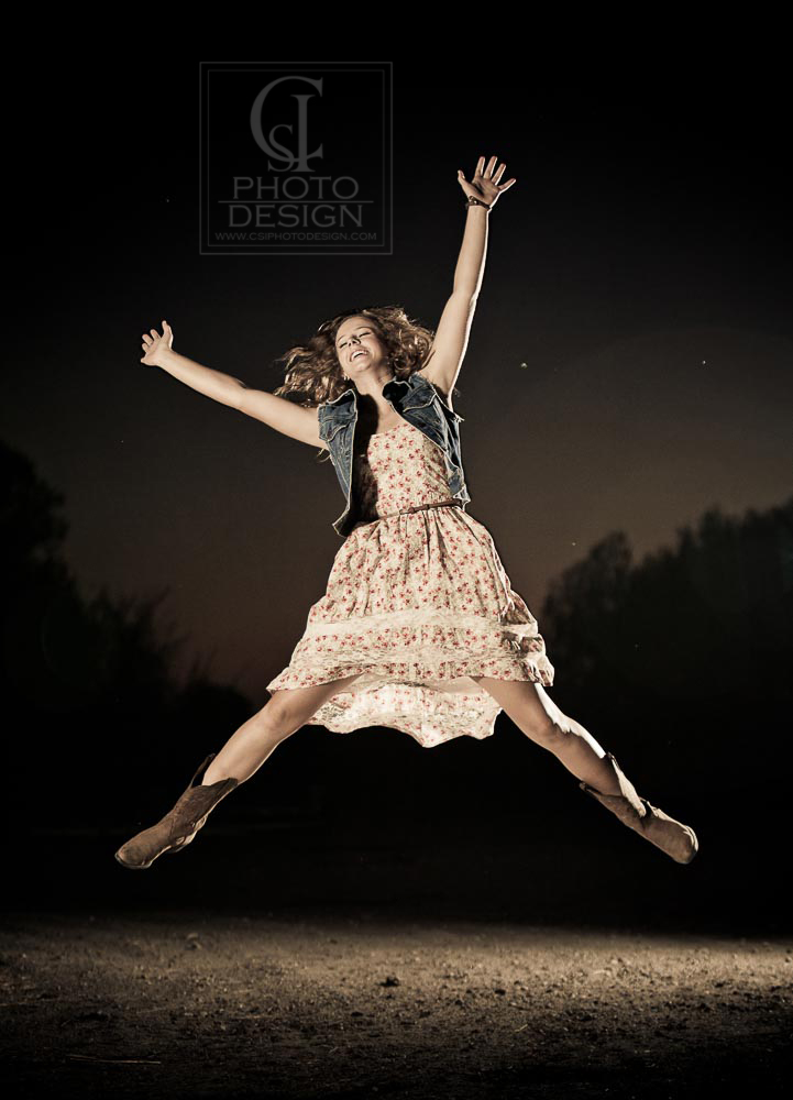 Senior girl leaping at twilight in a floral dress and denim vest