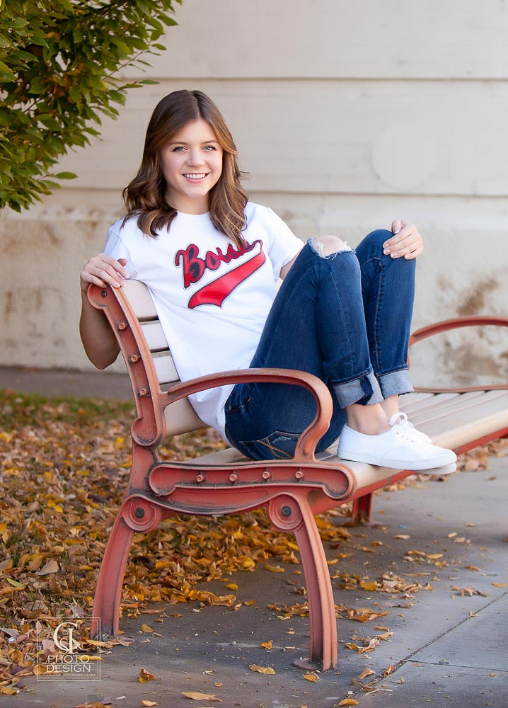 Senior girl in jeans white shoes and white top in the fall sitting on a bench