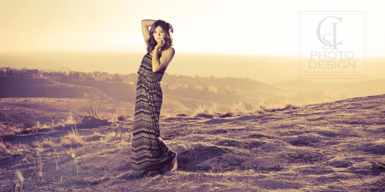 Senior girl in patterned long dress on top of a bluff at sunset