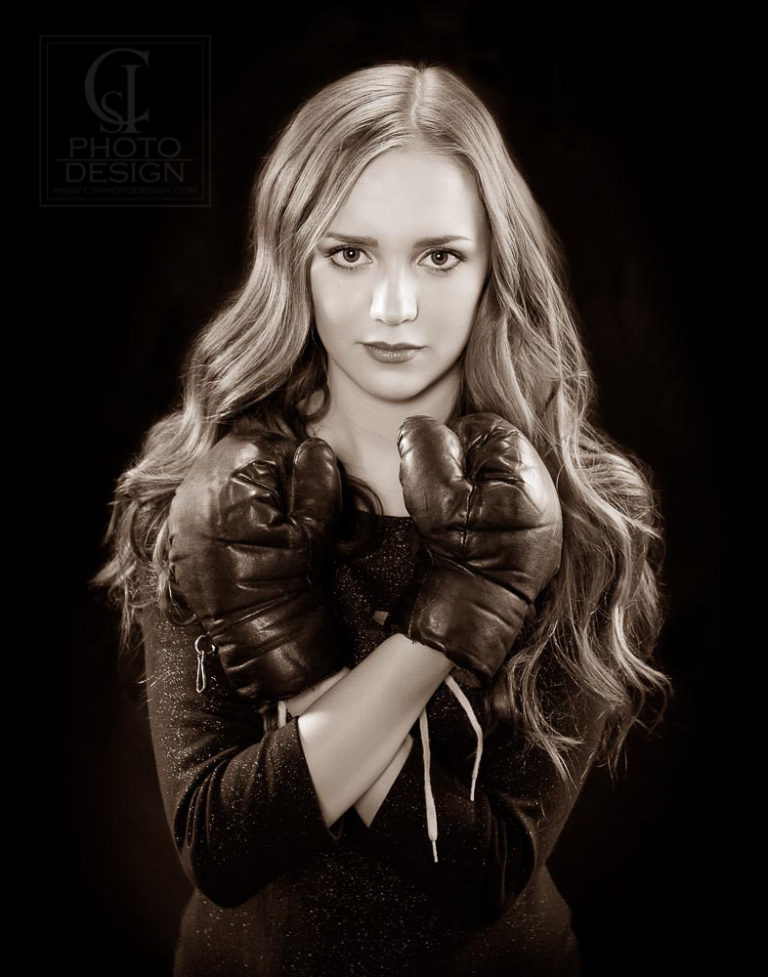 Senior girl with boxing gloves in front of a dark background in sepia