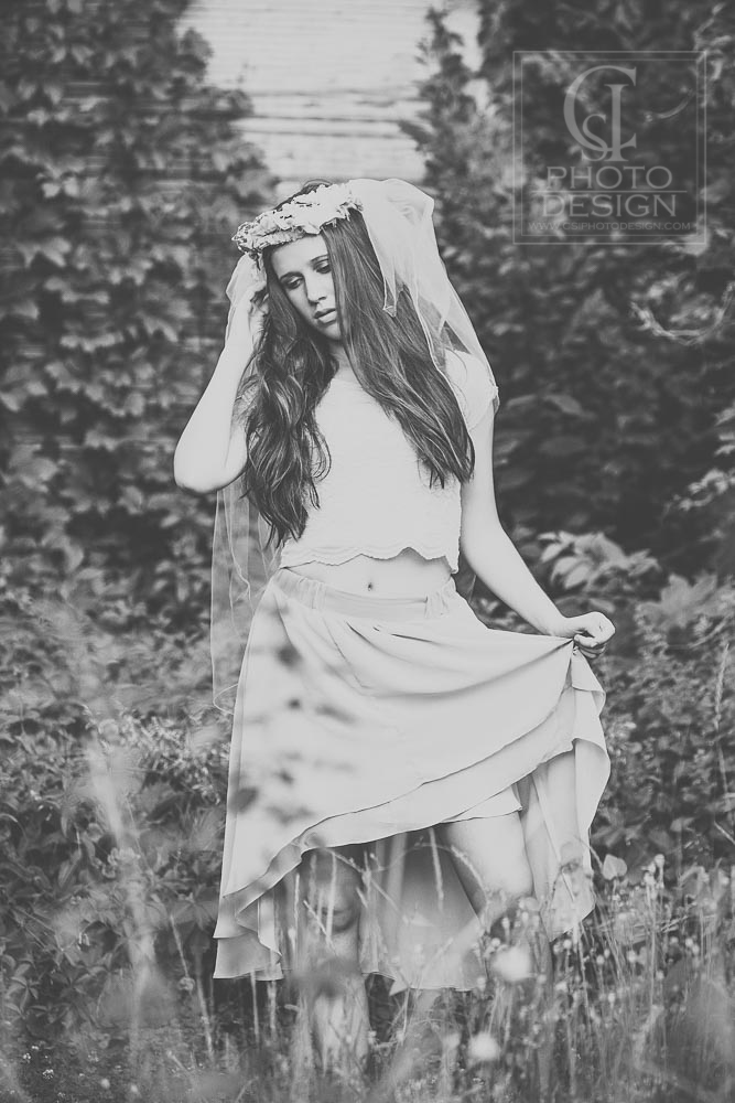 Senior girl in a light dress and floral headband looking down in black and white