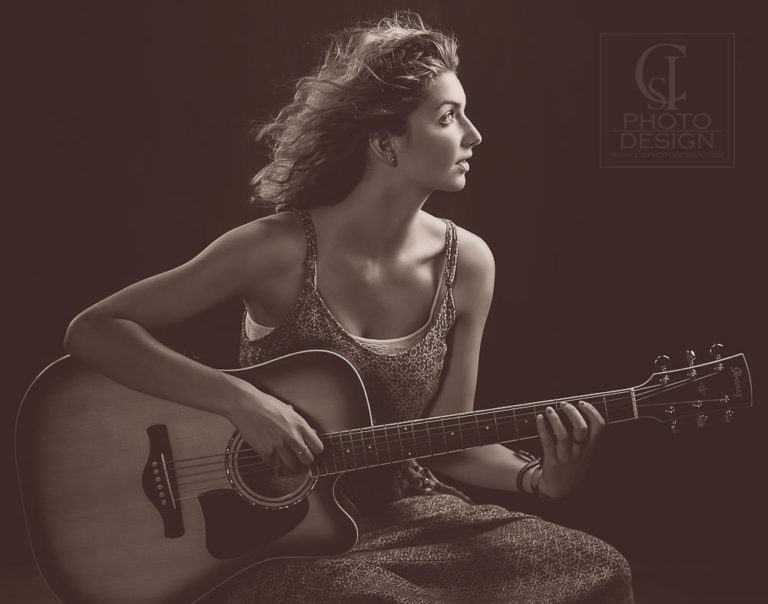 Senior girl playing guitar on dark studio background in sepia