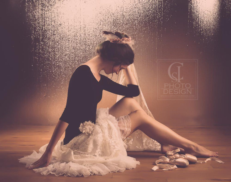 Senior girl in ruffled dress barefoot with ballet shoes in studio and reflective background