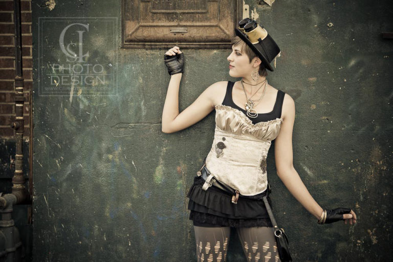 Senior girl in steampunk outfit on a green and textured wall