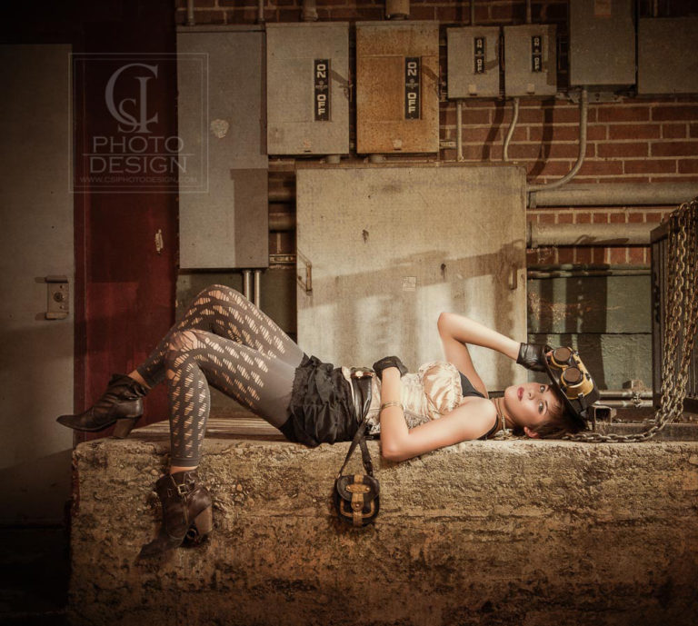 Senior girl in steampunk costume with electrical boxes and chains