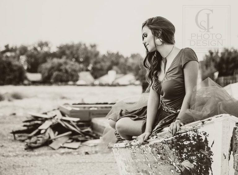 Senior girl sitting in a boat with wood pile in the background