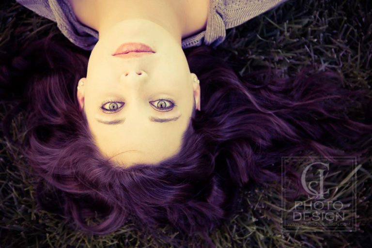 Senior girl with purple hair laying in the grass