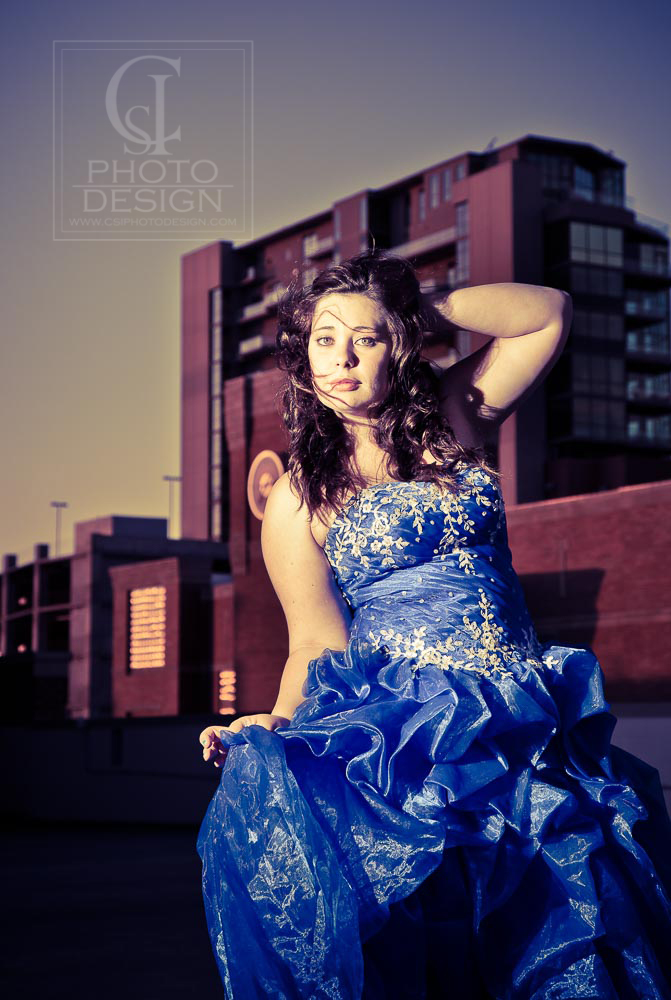 Senior girl in blue dress in front of modern urban building