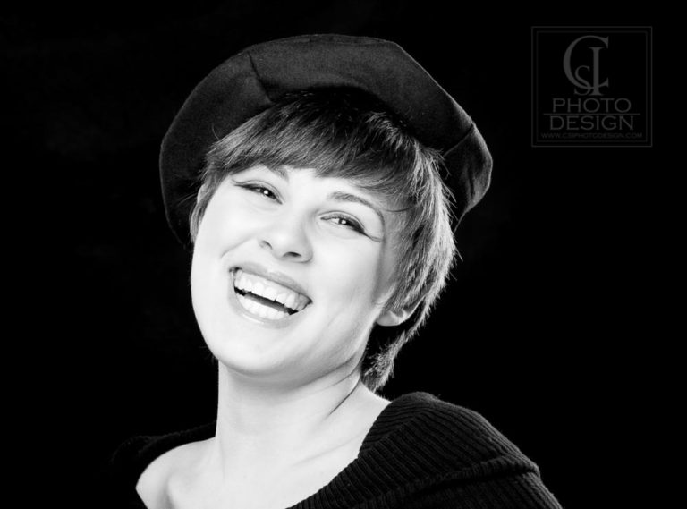 Senior girl in a black top and a beret in black and white