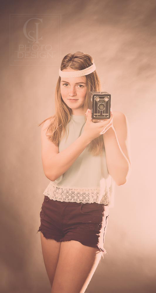 Senior girl in studio with white headband shorts and a camera