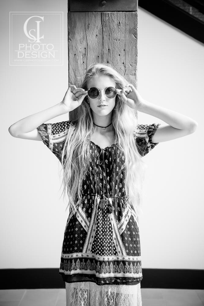 Senior girl in bohemian outfit with long blond hair and round sunglasses