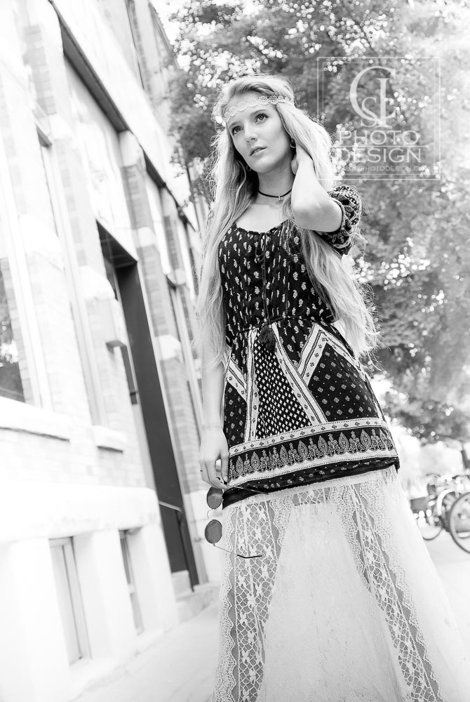 Senior girl in bohemian outfit standing on the sidewalk with lace skirt
