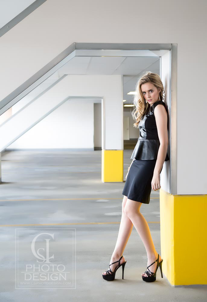 Senior girl in black dress and black heels and blond hair in a parking garage