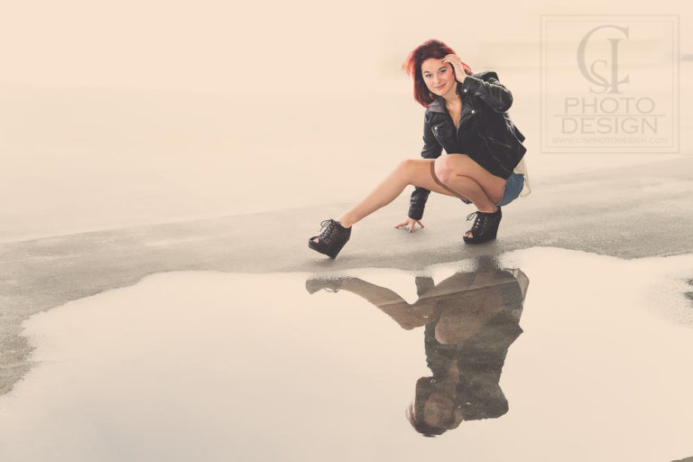 Senior girl in black leather denim shorts heels reflecting in a puddle