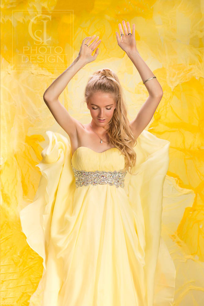 Senior girl in studio in a yellow dress against a yellow background