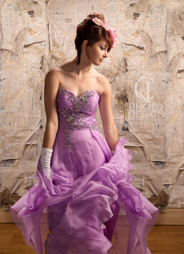 Senior girl in purple dress and white gloves floral headband with newsprint background