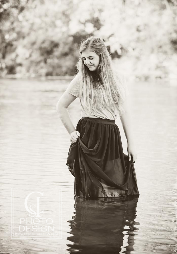 Senior girl in the water with a dark dress and long blond hair