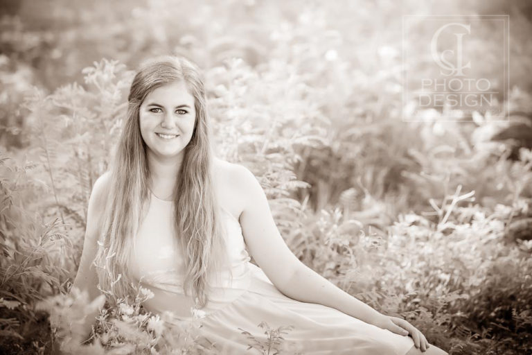 Senior girl with long blond hair and dress in sepia reclining in flowers and foliage