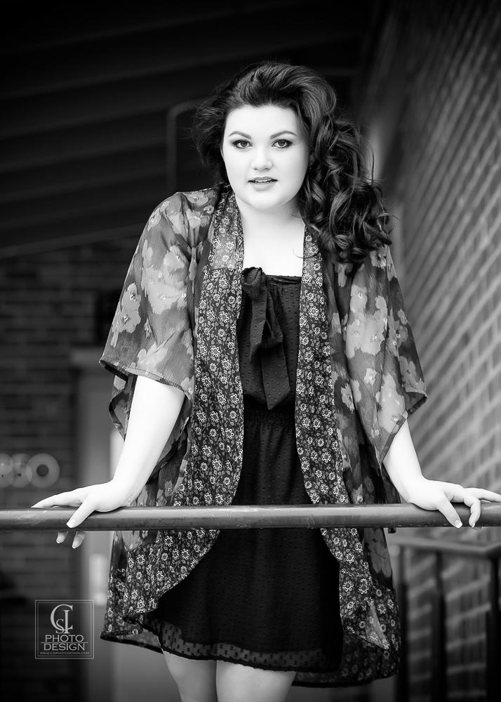 Senior girl in black dress and floral patterned top leaning against a railing