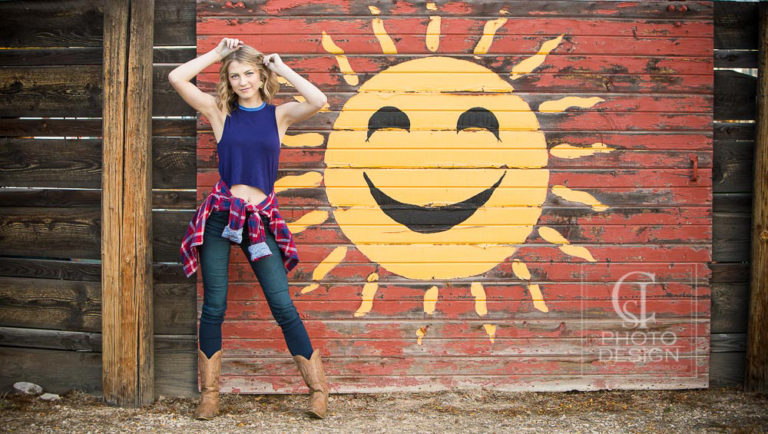 Senior girl with blue top jeans and boots with painted sun